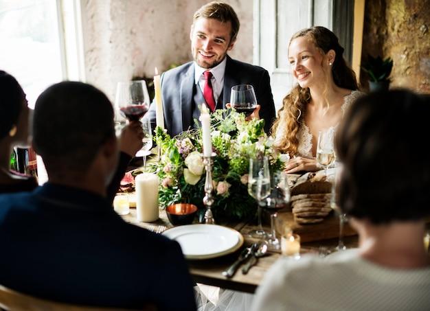 Bruid en bruidegom vastklampen wijnglazen met vrienden op huwelijksontvangst