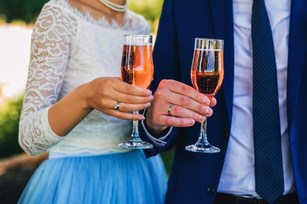 Bruid en bruidegom vieren de bruiloft met een glas champagne in hun handen met ringen