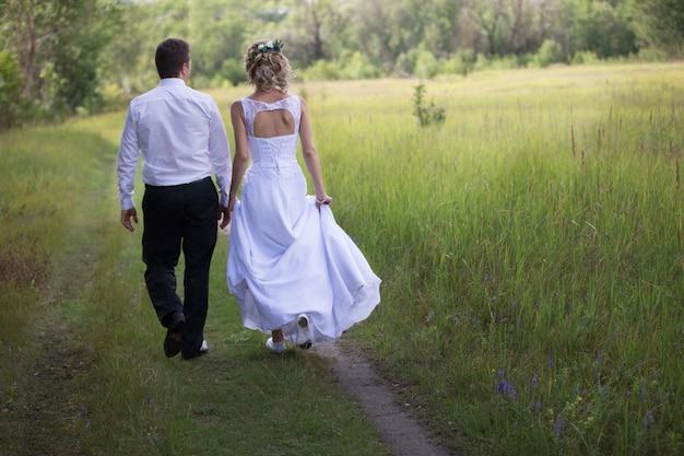 Bruid en bruidegom wandelen langs de bosweg