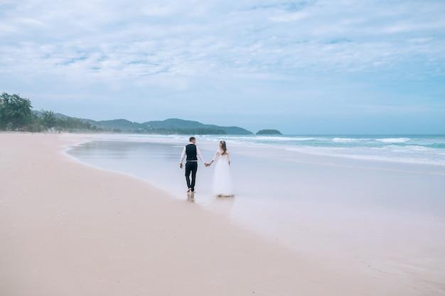 Bruid en bruidegom wandelen op het strand