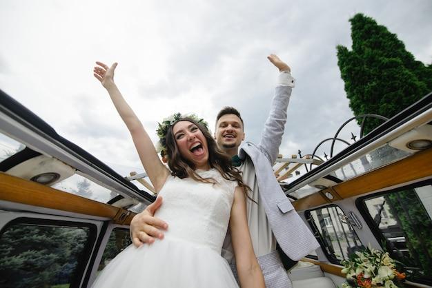 Bruid en bruidegom zitten achter het stuur van hun retro bus