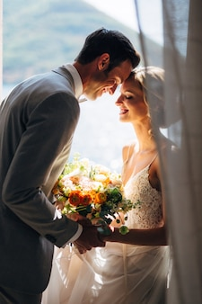 Bruid en bruidegom zitten bij het raam en knuffelen elkaar lachend