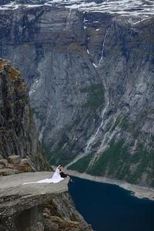 Bruid en bruidegom zittend op een fragment van rots in de bergen, tegen de achtergrond van de fjord
