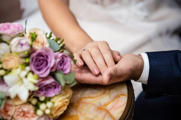 Bruid en bruidegomhanden met huwelijksboeket, concept tederheid en liefde.