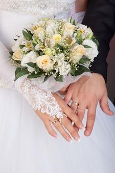 Bruid en bruidegomhanden met trouwringen en boeket rozen