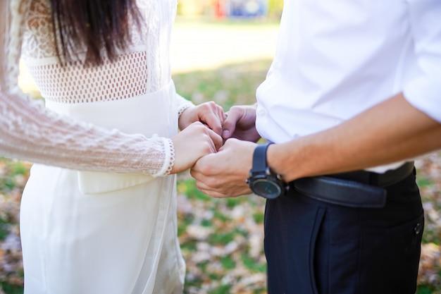 Bruid en bruidegomholdingshanden in openlucht