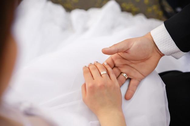 Bruid en bruidegomholdingshanden met huwelijk of verlovingsring