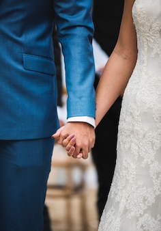 Bruid en bruidegomholdingshanden met liefde