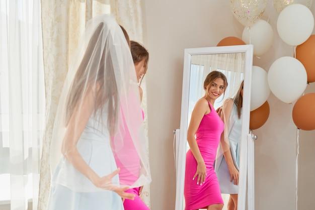 Bruid en bruidmeisje die klaar voor huwelijk worden.
