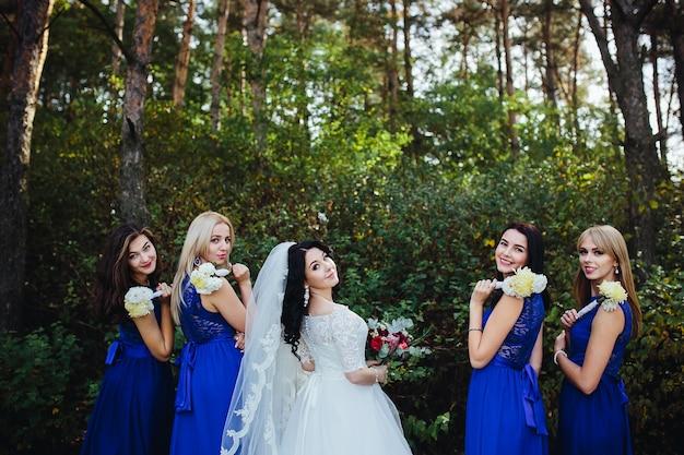 Bruid en bruidsmeisje kijken naar camera glimlachen