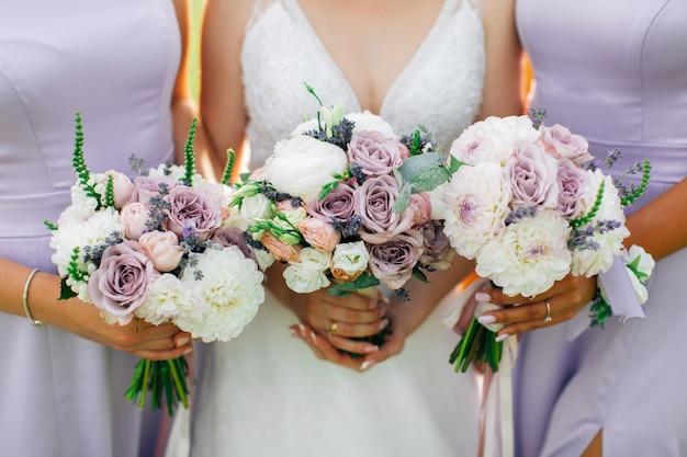 Bruid en bruidsmeisjes die boeketten van witte bloemen houden