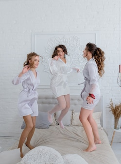 Bruid en bruidsmeisjes hebben plezier en springen op het witte bed