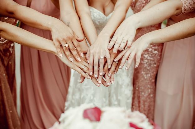Bruid en bruidsmeisjes in roze jurken rijken hun handen met