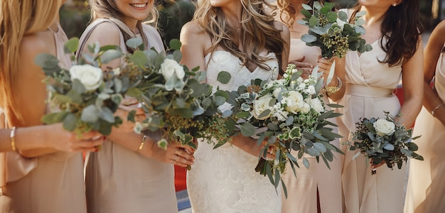 Bruid en bruidsmeisjes met pastel boeketten staan naast elkaar