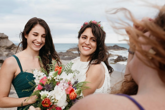 Bruid en bruidsmeisjes op het strand Gratis Foto