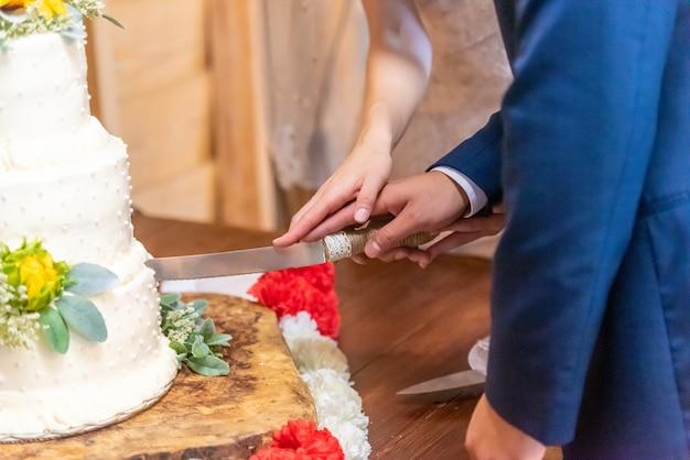 Bruid en een bruidegom die de mooie witte bruidstaart snijden