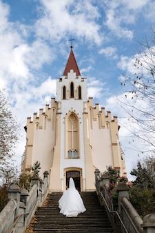 Bruid gaat op trappen naar de kerk