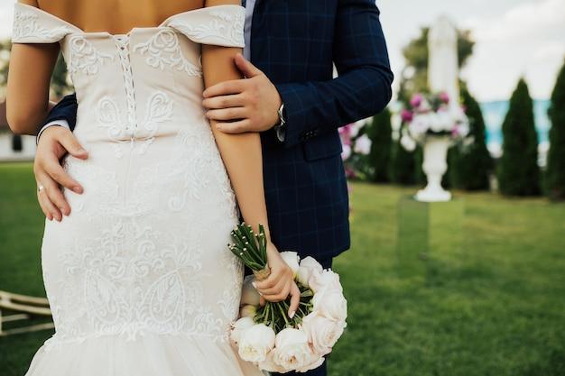 Bruid heeft een mooi boeket en bruidegom knuffelt haar voor rug.