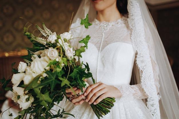 Bruid houdt bruiloft boeket van witte bloemen in haar hand