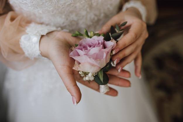 Bruid houdt een butonholle met roze roos