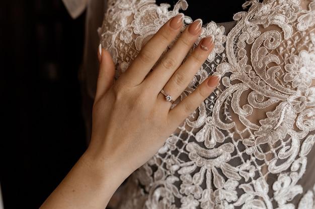Bruid houdt haar hand op opgehangen bruidsjurk
