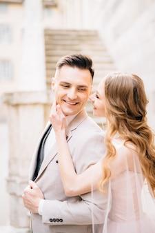 Bruid houdt haar handpalm op de kin van de glimlachende bruidegom
