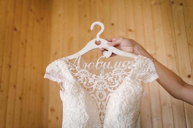 Bruid houdt trouwjurk op hanger met hand