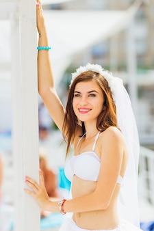 Bruid in beha en bruidssluier. jonge vrouw glimlacht en houdt behin