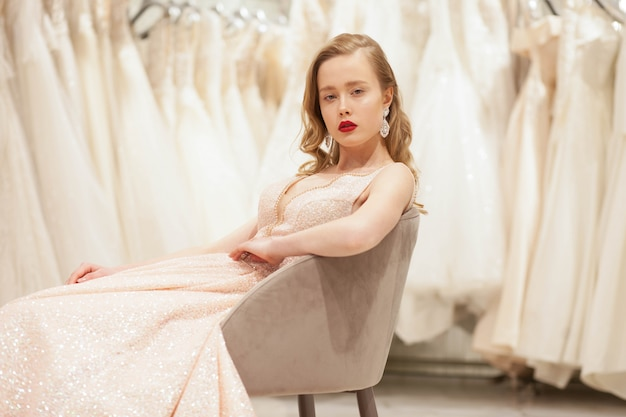 Bruid in chique jurk poseren op stoel in bruiloft salon