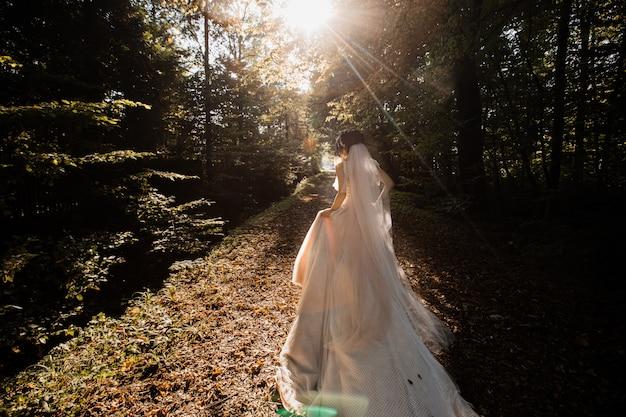 Bruid in de lange trouwjurk gaat op het bospad
