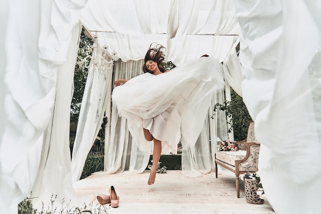 Bruid in de lucht. volledige lengte van aantrekkelijke jonge vrouw in trouwjurk die lacht terwijl ze buiten in het huwelijkspaviljoen springt