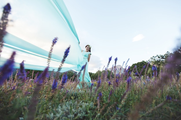 Bruid in de natuur in de bergen bij het water. jurk kleur tiffany. de bruid speelt met zijn jurk.