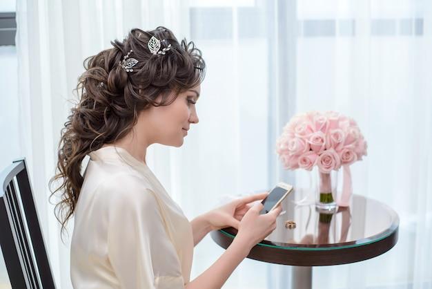 Bruid in de ochtendzitting bij het venster met de telefoon