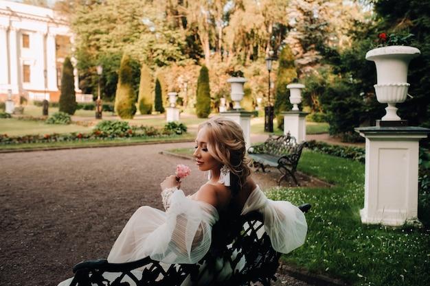 Bruid in de tuin, bruid zittend op een bankje, bruid die samenkomt, ochtendbruid, witte jurk, oorringen op.