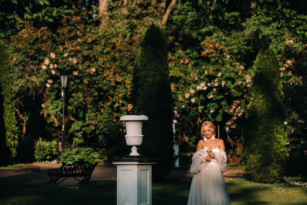 Bruid in de tuin, ochtend en bruid, bruidsprijzen, ochtendbruid, witte jurk, oorbellen dragen.
