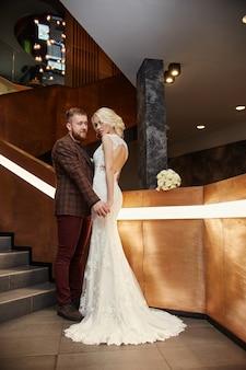 Bruid in een chique lange jurk met een trein en de bruidegom staan op grote trappen