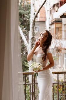 Bruid in een elegante witte trouwjurk met een boeket bloemen