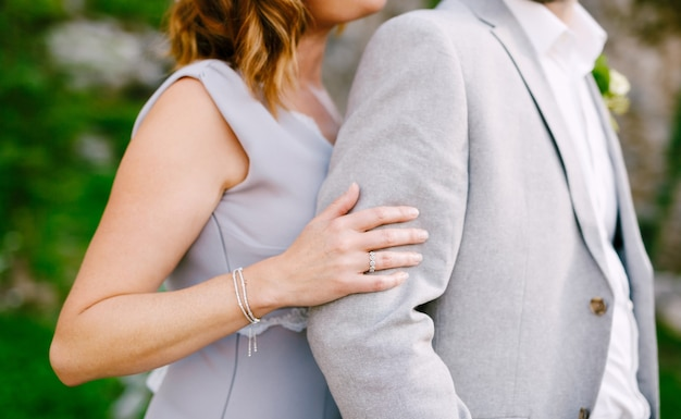 Bruid in een grijze jurk knuffels van achter bruidegom in een grijs pak