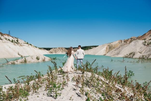 Bruid in een mooie jurk hand in hand met de bruidegom in een licht pak tegen de blauwe lucht en het blauwe water. bruidspaar staande op een zanderige heuvel in de open lucht.