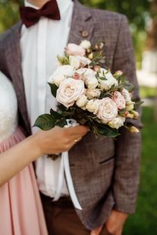 Bruid in een mooie jurk met een trein met een boeket bloemen en groen