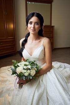 Bruid in een mooie witte jurk en een boeket bloemen in haar handen wacht op de huwelijksceremonie. mooie vrouw met een bruidsboeket in haar handen