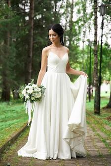 Bruid in een mooie witte jurk en een boeket bloemen