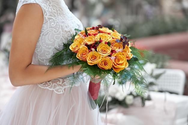 Bruid in een mooie witte jurk gaat met een bruiloft boeket oranje rozen in haar handen
