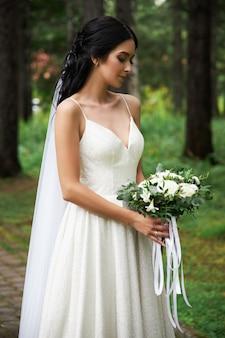 Bruid in een mooie witte jurk met een boeket bloemen