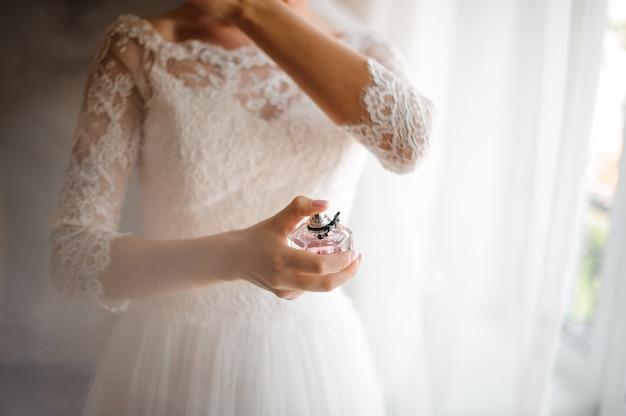 Bruid in een mooie witte trouwjurk met een parfum