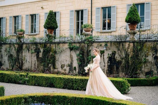 Bruid in een roze jurk met een boeket bloemen loopt door de tuin