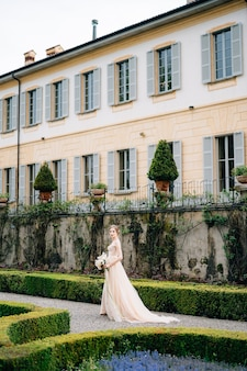 Bruid in een roze jurk met een boeket bloemen loopt door het park bij de oude villa