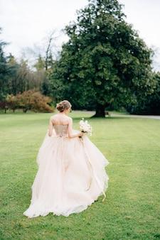 Bruid in een roze jurk met een boeket bloemen loopt in een groen park