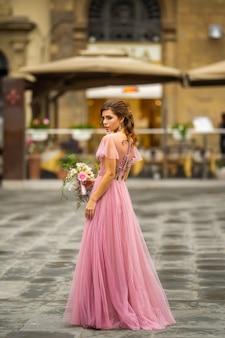 Bruid in een roze jurk met een boeket staat in het centrum van de oude stad van florence in italië.