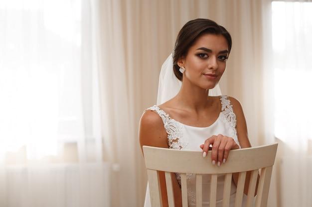 Bruid in een stijlvolle jurk en lange sluier op een stoel binnen